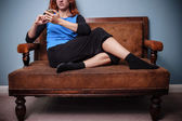 Young woman sitting on old sofa texting on her phone — Stock Photo