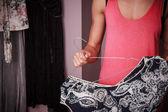 Mladá žena uspořádání oblečení doma — Stock fotografie