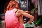 Elbiselerini evde ütü ve tv seyretmek genç kadın — Stok fotoğraf