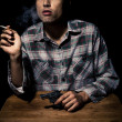 Atmospheric shot of man with gun smoking cigarette — Stock Photo