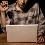 Cigarette smoking man working on laptop — Stock Photo