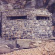 Old world war two bunker on the beach surrounded by rocks — Stock Photo