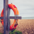 Life buoy on post at the beach — Stock Photo