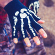 Woman wearing skeleton glove on the beach — Foto Stock