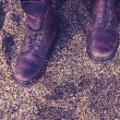 Woman's boots on pebble beach — Stock Photo