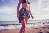 Young woman in colorful skirt walking on the beach — Stock Photo