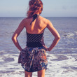 Rear view of young woman standing on beach looking at sea — Stock Photo