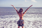 Young woman raising her arms at the beach — Stock Photo