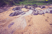 Stream of water on beach with near rural landscape — Stock Photo