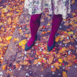 Woman standing amongst leaves and confetti — Stock Photo