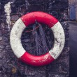 Life buoy on old stone wall — Stock Photo