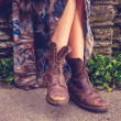Woman's legs and hiking boots by stone wall — Stock Photo #35097329
