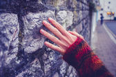 Woman touching an old stone wall — Foto de Stock