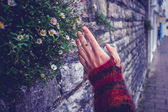Woman touching an old stone wall — Stockfoto