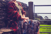 Woman relaxing by rural stone wall — Stockfoto
