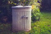 Old metal trashcan in a garden — Stock Photo