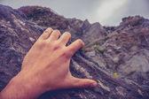Man's hand on rock — Stock Photo