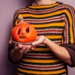 Young woman holding a scary jack-o-lantern — Stock Photo