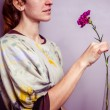 Young woman holding a single purple flower — Stock Photo