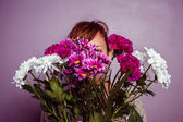 Young woman hiding behind a bouquet of flowers — Stockfoto