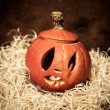 Scary Halloween pumpkin on hay — Stock Photo