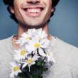Happy young man with flowers — Stock Photo