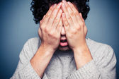 Young man hiding his head in his hands — Stock Photo