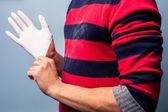 Man putting on latex glove — Stock Photo