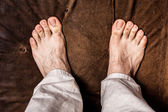 Man's bare feet on brown texture — Stock Photo