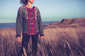 Hopeful young woman standing in meadow by the sea at sunset — 图库照片