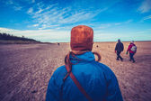 Young woman and hikers on the beach — Stock Photo