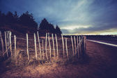 Old fence on the beach at sunset — Stock Photo