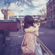 Young woman looking at street and railway line — Foto Stock