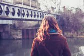 Young woman by canal and rail bridge — Stockfoto