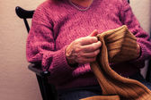 Old woman mending a jumper at home — Stock Photo