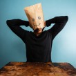 Man with bag over head relaxing at desk — Stock Photo