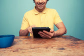 Young man at table reading on tablet — Stock Photo
