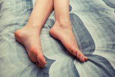 Feet of young woman on bed at home — Stock Photo