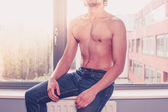 Shirtless man at the window — Stock Photo