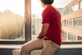 Young man on window sill — Stock Photo