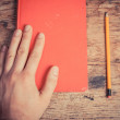 Stock Photo: Hand with book and pencil