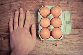 La main sur table avec boîte d'oeufs — Photo