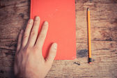 Hand with book and pencil — Stock Photo