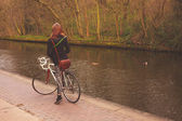 Woman on bicycle by canal — Stock fotografie