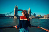 Young woman on boat looking at Tower Bridge in London — Stock Photo