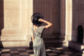 Elegant young woman standing in a grand hall — Stock Photo