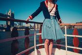 Young woman on the deck of ship with skirt blowing in the wind — Stock Photo
