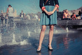 Young woman standing by fountain in city on a hot day — Stock Photo