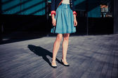 Young woman in skirt standing in the street — Stok fotoğraf