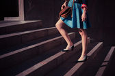 Young woman walking up stairs — Stok fotoğraf